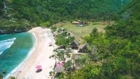 Lila Sunbed на красивом идилличном белом пляже Atuh песка Ясные голубые океанские волны свертывая к пляжу Nusa Penida, Бали Стоковые Фотографии RF