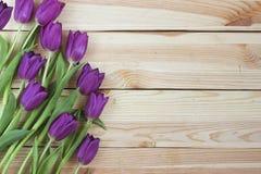 Lila Tulpen auf planked hölzernem Hintergrund von oben, Feiertagsde Stockfotos