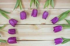 Lila Tulpen auf planked hölzernem Hintergrund von oben, Feiertagsde Lizenzfreie Stockbilder