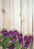 Lila Tulpen auf planked hölzernem Hintergrund von oben, Feiertagsde Stockbilder