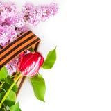 Lila y tulipán, atados con una cinta de San Jorge en un backgr blanco Fotografía de archivo libre de regalías