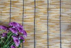 Lilablommor som förläggas på vävde rullgardiner 1 för ett trä Arkivfoto