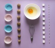 Lilac background food knolling walnut greek seeds sunflower sugar cube refined corolla egg in round bowl cake mold flour blue pink royalty free stock photos