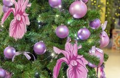 Lilac balls and orchid flowers on the Christmas tree stock images
