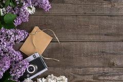 Lilac bloesem op rustieke houten achtergrond met lege ruimte voor groetbericht Camera, kleine envelop Hoogste mening Royalty-vrije Stock Foto
