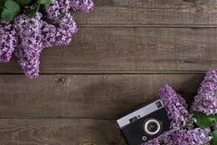 Lilac bloesem op rustieke houten achtergrond met lege ruimte voor groetbericht Oude camera Hoogste mening Royalty-vrije Stock Fotografie