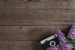 Lilac bloesem op rustieke houten achtergrond met lege ruimte voor groetbericht Oude camera Hoogste mening Stock Foto's