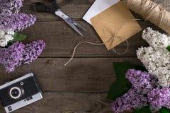 Lilac bloesem op rustieke houten achtergrond met lege ruimte voor groetbericht Schaar, draadspoel, kleine envelop Stock Foto's