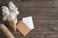 Lilac bloesem op rustieke houten achtergrond met lege ruimte voor groetbericht Schaar, draadspoel, kleine envelop Royalty-vrije Stock Afbeelding