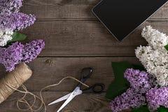 Lilac bloesem op rustieke houten achtergrond met lege ruimte voor groetbericht Tablet, schaar, draadspoel Hoogste mening Stock Foto's