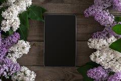 Lilac bloesem op rustieke houten achtergrond, tablet met lege ruimte voor groetbericht Hoogste mening Royalty-vrije Stock Foto