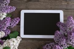 Lilac bloesem op rustieke houten achtergrond, tablet met lege ruimte voor groetbericht Hoogste mening Stock Foto