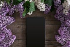 Lilac bloesem op rustieke houten achtergrond, tablet met lege ruimte voor groetbericht Hoogste mening Royalty-vrije Stock Afbeeldingen