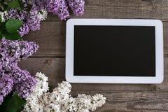 Lilac bloesem op rustieke houten achtergrond, tablet met lege ruimte voor groetbericht Hoogste mening Stock Afbeelding