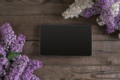 Lilac bloesem op rustieke houten achtergrond, tablet met lege ruimte voor groetbericht Hoogste mening Royalty-vrije Stock Fotografie