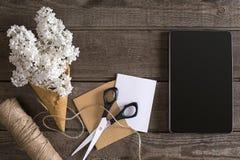 Lilac bloesem op rustieke houten achtergrond, tablet met lege ruimte voor groetbericht Schaar, kleine draadspoel, Royalty-vrije Stock Fotografie