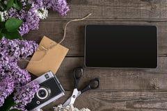 Lilac bloesem op rustieke houten achtergrond, tablet met lege ruimte voor groetbericht Schaar, kleine draadspoel, Stock Afbeelding