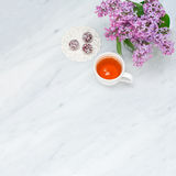 Lilac blossom branches, cup of tea and bliss balls on Carrara ma Stock Image