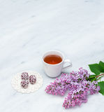 Lilac blossom branches, cup of tea and bliss balls on Carrara ma Royalty Free Stock Image