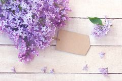 Lilac branch with empty paper tag. On white wooden table Royalty Free Stock Image