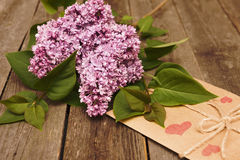 Lilac branch on wooden background, Valentine`s Day and Mothers. Background for congratulation on holiday, Valentine`s Day, flowers on wooden table Stock Photo