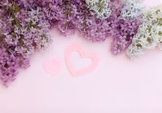 Lilac branches and two pink heart on a light pink background empty space for your text, top view. stock photos