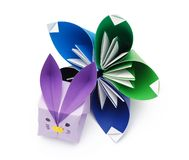 Lilac bunny and an origami flower. Little lilac and purple origami bunny sitting in front of a big green and blue origami flower royalty free stock photos