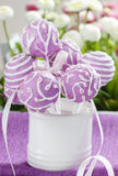 Lilac cake pops in white ceramic jar. White and pink daisies in the background. Party table setting Stock Photos
