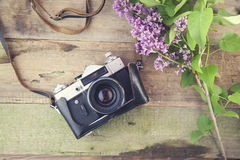 Lilac and camera. On wooden table Stock Photo