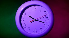 Lilac Clock on color wooden plank wall, night. Lilac Clock on color wooden plank wall. white office clock on colorful background. night stock footage