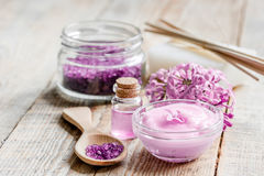 Lilac cosmetics with flowers and spa set on wooden table background Royalty Free Stock Photography