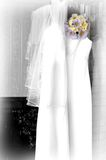 Lilac Daisies on Wedding Dress. Black and white picture with gentle splash of color from lilac Daisies.  Wedding dress has veil hanging over the shoulder Stock Photos