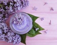 Lilac de zorgtak van de room kosmetische regeneratie bij het roze houten harmonie bevochtigen stock afbeelding