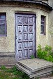 Lilac door on the old wall with windows Royalty Free Stock Images
