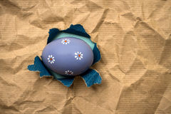 Lilac Eastern egg in hole  brown wrapping paper Royalty Free Stock Photography