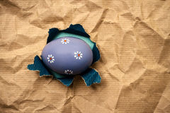 Lilac Eastern egg in hole  brown wrapping paper Stock Photography