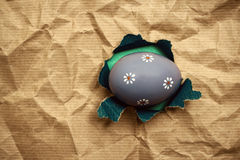 Lilac Eastern egg in hole  brown wrapping paper Royalty Free Stock Images