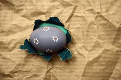 Lilac Eastern egg in hole  brown wrapping paper Royalty Free Stock Photos