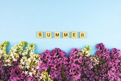 Lilac flower blooming background. Summer wooden lettres text, concept clipart. Closeup floral frame