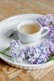 Lilac flower bouquet, wood desk, white background, morning. Lilac flower and a cup of tea on the wood delivery desk. White background Stock Photos