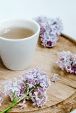 Lilac flower and a cup of tea on the wood delivery desk. White background. Lilac flower bouquet, wood desk, white background, morning Stock Images