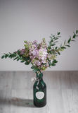 Lilac flower in a green vase on  wooden background. Lilac flower in a green vase on a wooden background Royalty Free Stock Image