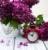 Lilac flowers with alarm clock Royalty Free Stock Photo