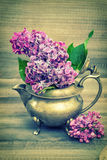 Lilac flowers in antique vase on wooden background. Vintage styl Royalty Free Stock Photo