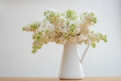 Lilac flowers bunch in a basket over blurred wood background. White Lilac flowers bunch in a basket over blurred wood background royalty free stock photo