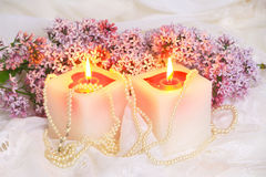 Lilac flowers and candle Stock Images
