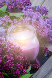 Lilac flowers with candle. Fresh violet lilac flowers with burning candle Stock Images