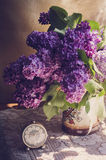 Lilac flowers in a ceramic pot with vintage tiny alarm clock Stock Photography