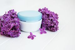 Lilac flowers and cosmetic cream. On a white wooden background Stock Image