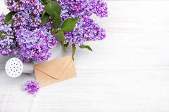 Lilac flowers and envelope on white wooden background, Royalty Free Stock Photo